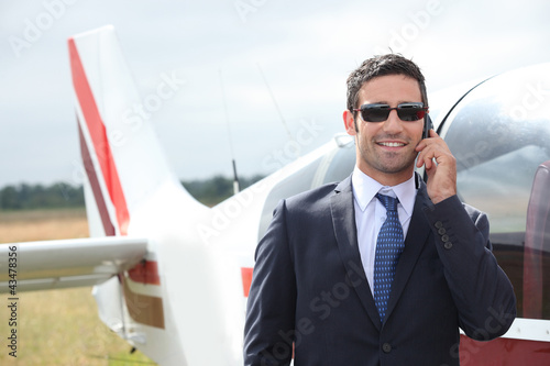 Man talking on a mobile phone next to a private plane