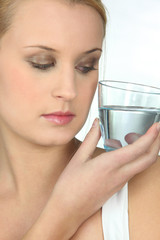 Woman looking at a glass of water