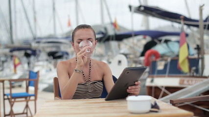 Young woman with tablet computer sitting in marina