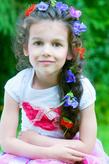 Adorable little girl with flowers in hair outdoors