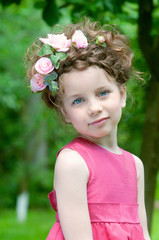 Adorable little girl with roses in hair outdoors