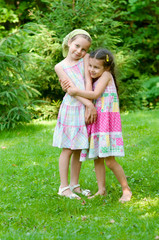 Two adorable little girls standing together in the park
