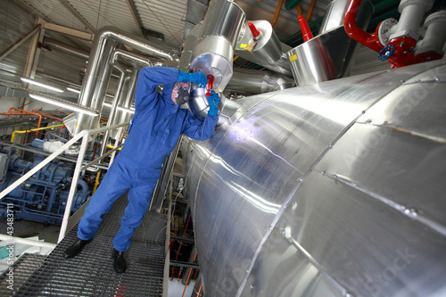 Technician in  blue uniform reparing technological system