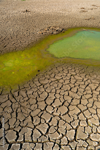 Polluted water and cracked soil of dried out lake during drought