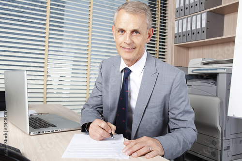 handsome businessman reads the agreement