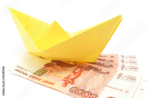 Yellow paper ship upon ruble notes isolated over white