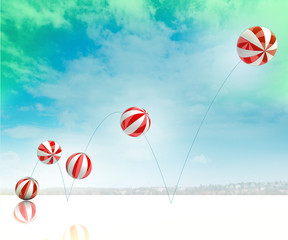 five jumping white red striped inflatable balls