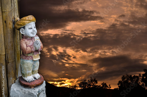 Thai Children doll on sunrise background.