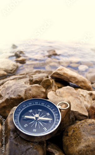 Leinwanddruck Bild compass on the shore