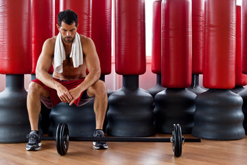 Handsome muscular man sitting in front of red punching bags.