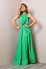 Portrait of the beautiful woman in a long green dress.
