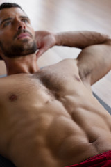 Handsome muscular man doing sit-ups.