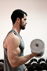 Handsome muscular man lifting weights.
