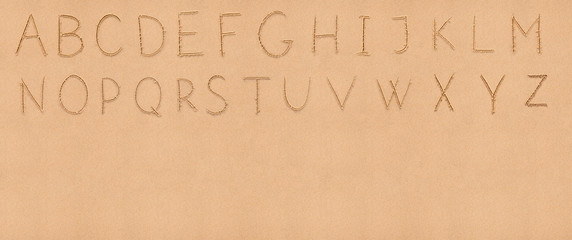 Handwriting English alphabet on flat sand with empty space appro