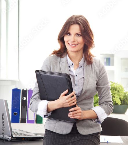 A young brunette businesswoman holding a black folder