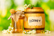 Sweet honey in barrel and jar with acacia flowers