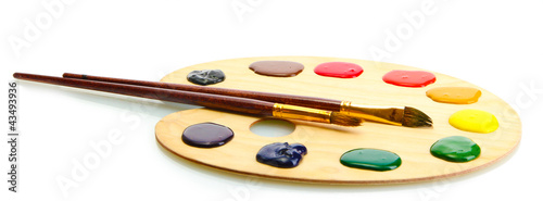 wooden art palette with  paint and brushes.isolated on white