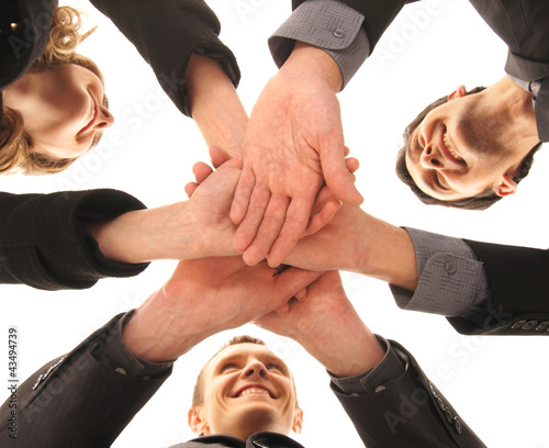 Three young business persons in a group handshake