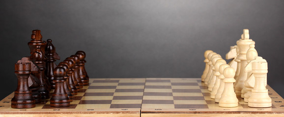 Chess board with chess pieces on grey background