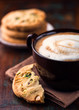 Cup of cafe au lait and pistachio cookies