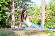 Beautiful woman doing  joga exercising on the grass in forest