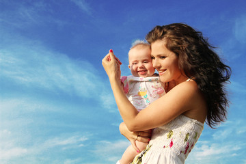 happy mother with baby over blue sky