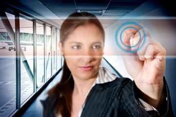 Busines woman at airport touching digital screen