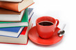 A stack of books and a cup of coffee in a saucer on a white back