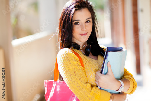 pretty female university student holding books