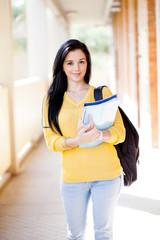 pretty female university student walking down school corridor