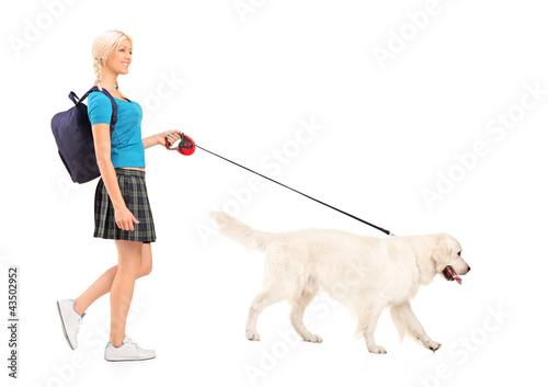 Full length portrait of a female student walking a dog