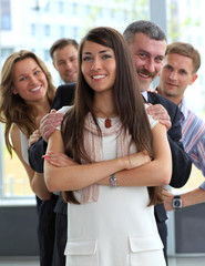 happy young female business leader stading in front of her team