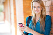 happy young woman sending sms with cell phone