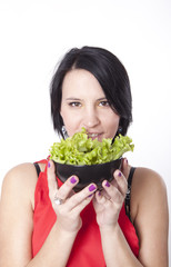 Young attractive woman eating green salad