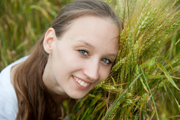 Beautiful woman smiles in a wheat  field