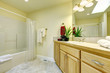 Simple large bathroom with tub and wood cabinets.