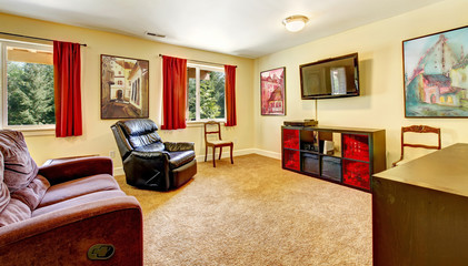 Tv living room with art and red curtains and beige carpet.
