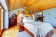 Blue bedroom with wood ceiling and fireplace interior.