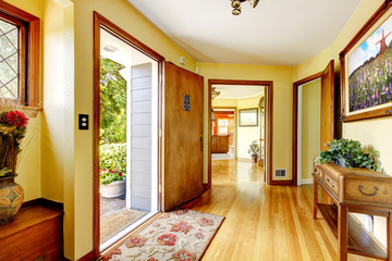 Large old luxury house entrance with art and yellow walls.