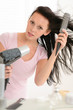 Woman blow-drying hair using round hairbrush
