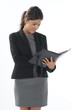 Self confident female  executive holding notebook in her hands.