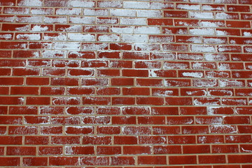 Old red brick wall with white paint splatter