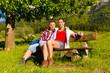 Glückliches Paar sitzt auf Bank vor Bergpanorama