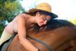 Girl in straw hat hugs her horse