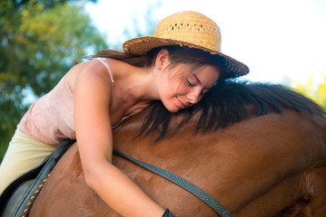 Girl in straw hat hugs her horse