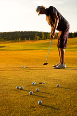 Male golf player practicing a par during sunset