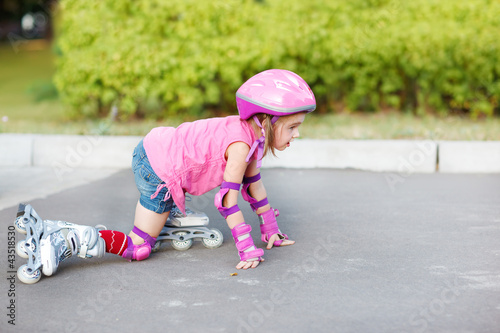 Girl in roller skates getting up