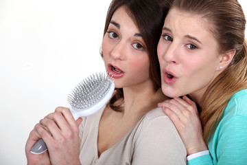 Two girl singing into hairbrush
