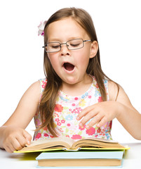 Cute little girl is yawning while reading book