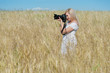 Beautiful woman take a photo with camera in a field